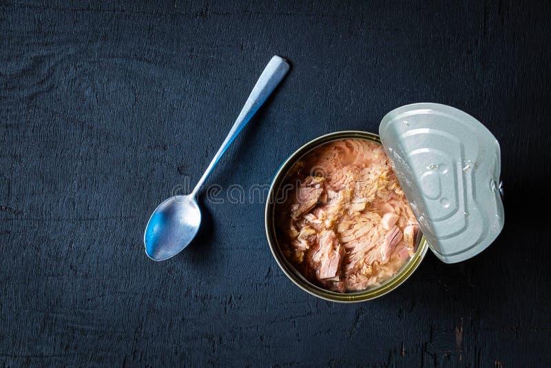 Mat p? burk och tonfisk p? burk in p? svart bakgrund arkivfoto