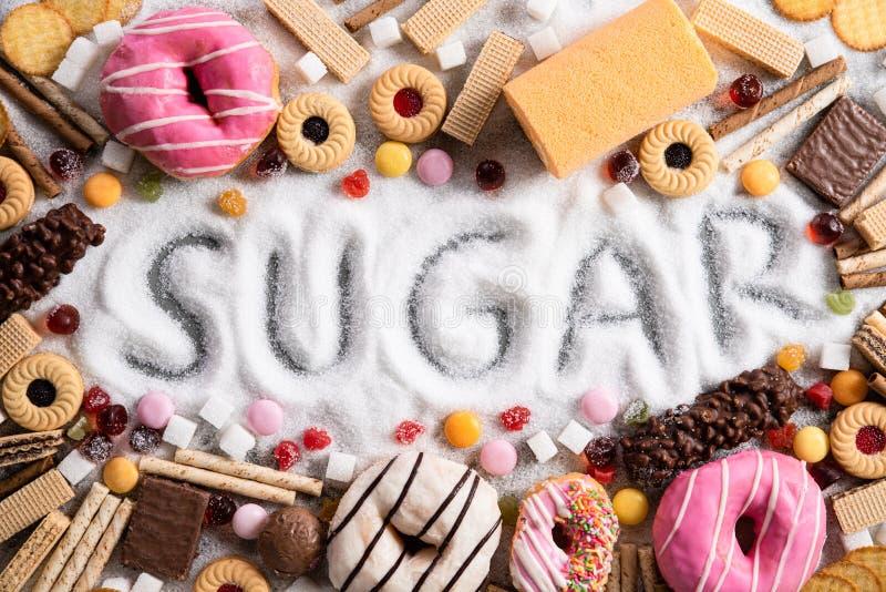 Mat som innehåller socker blandning av söta donuts, kakor och godisen med sockerspridning och skriftlig text i sjuklig näring, ch royaltyfri fotografi