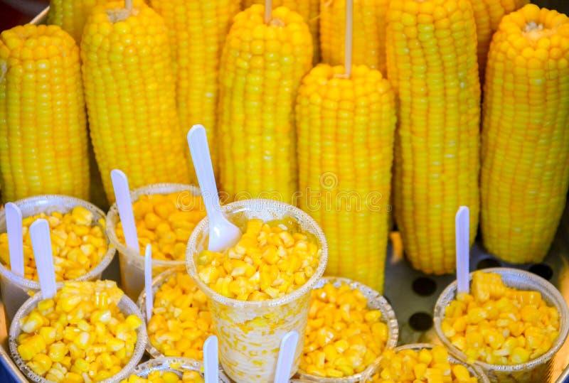 Mat stannar, gatamat på att gå gatamarknaden, kokade majs på pinnen och skivad havre i plast- kopp fotografering för bildbyråer