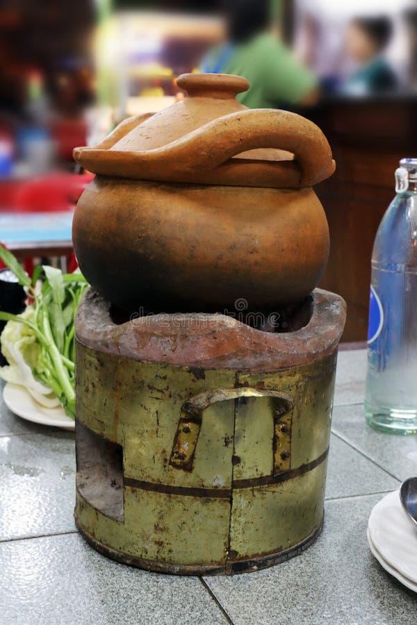 Mat thai asia, dopp som för lerakrukor doppar krukan på den gamla spisen, söt chili som doppar krukan i soppa, ragu i en lerakruk arkivbilder
