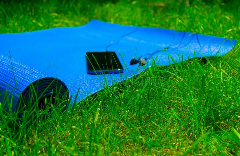 Mat voor yoga en pilates, telefoon met hoofdtelefoons op groen gras, concept opleiding en sporten in aard stock foto