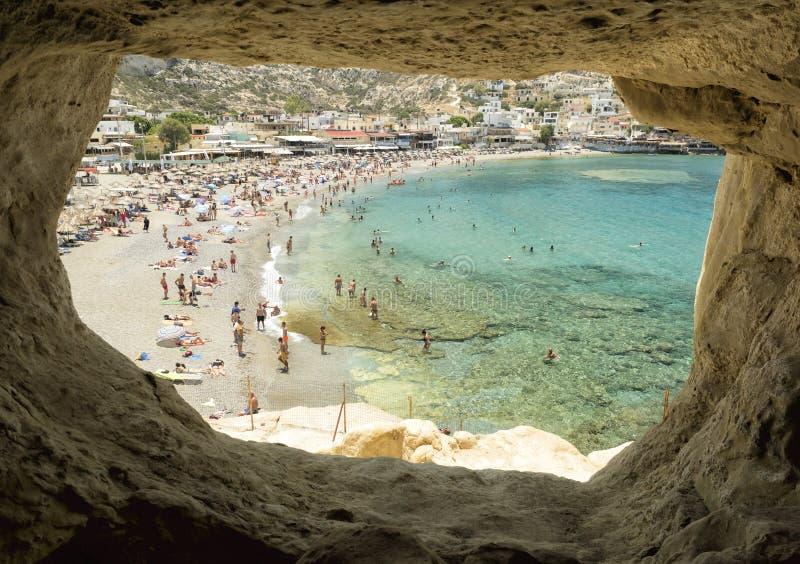 Matala的游人靠岸,从洞的一个看法,克利特海岛,希腊- 2018年6月22日 库存照片