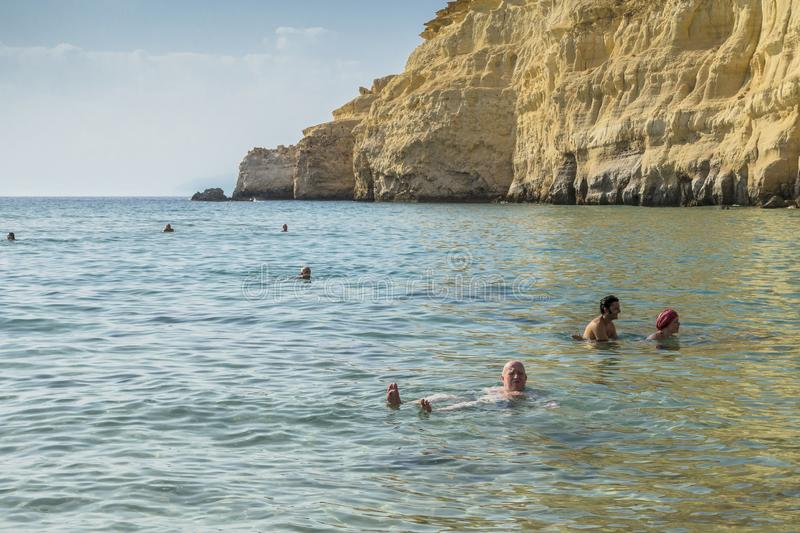 Matala , Red beach. Red Beach, near Matala, Crete, Greece , Europe . Nudist and hippie beach. People swimming in the sea water royalty free stock photos