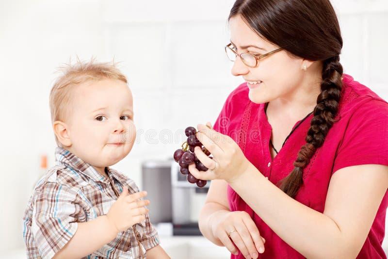 Matande barn för moder med druvan arkivfoto