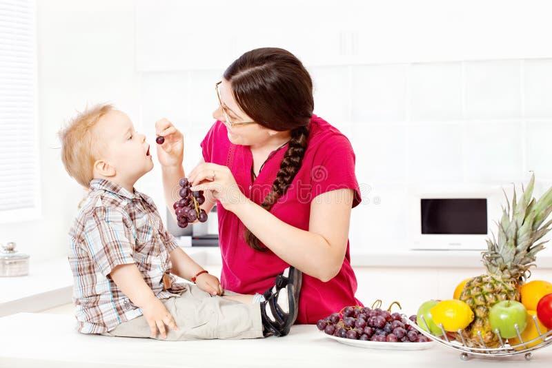 Matande barn för moder med druvor fotografering för bildbyråer