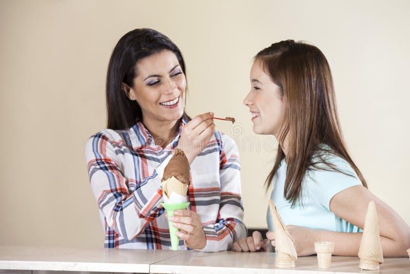 Matande glass för kvinna till dottern i mottagningsrum arkivfoto