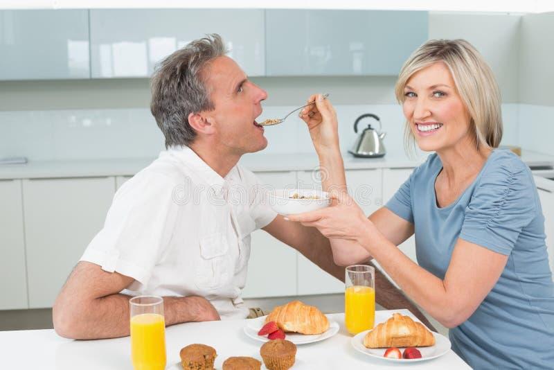 Matande man för kvinna på frukosttabellen i kök royaltyfria bilder
