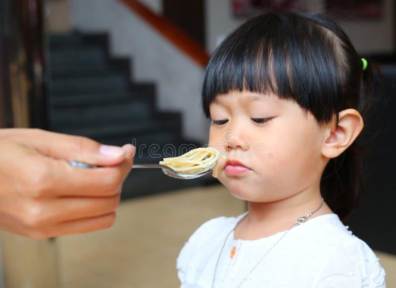 Matande spagetti för moder på skeden för hennes unge royaltyfria foton