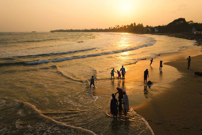 Matara, Шри-Ланка, 04-15-2017: Золотой заход солнца в тропиках на океане Силуэт людей идя вдоль пляжа и воды стоковое изображение