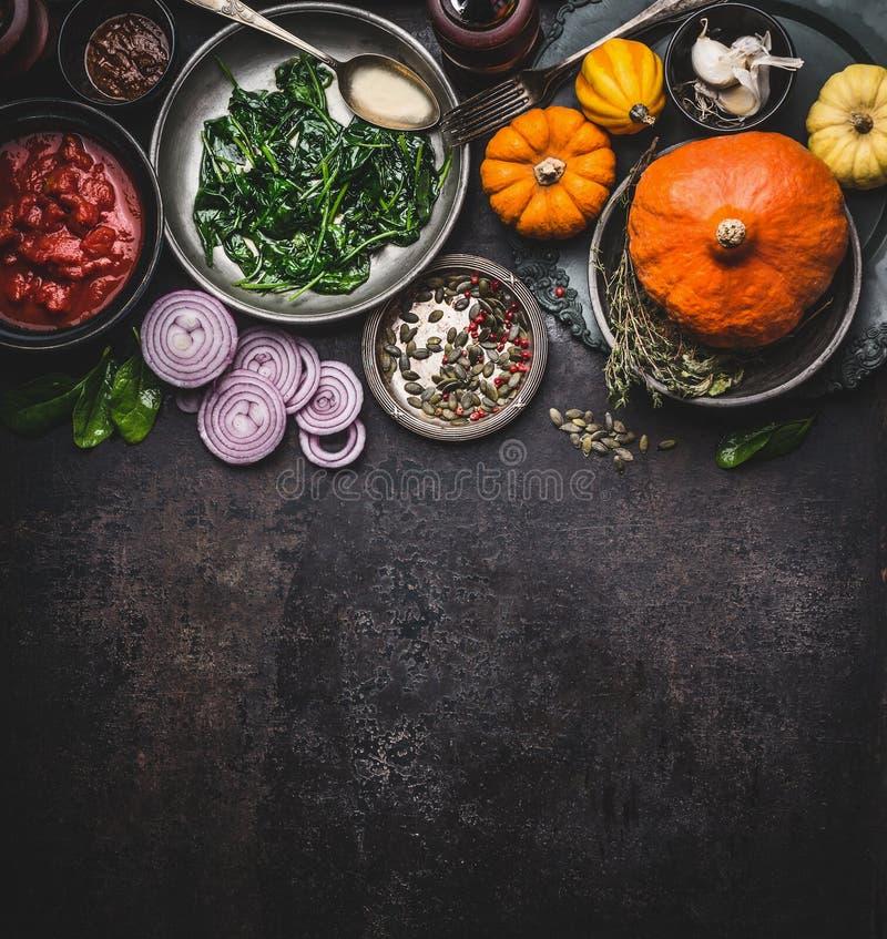 Matbakgrund för sunda vegetariska matlagningingredienser för smaklig pumpa besegrar recept i bunkar: tomatsåser, spenat, sli arkivbilder