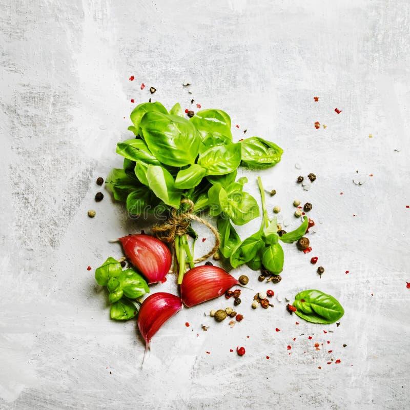 Matbakgrund, grön basilika, vitlök, saltar och pepprar, den bästa sikten royaltyfri foto