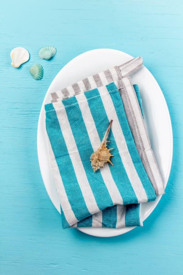 Matbakgrund i marin- stil Den marin- tabellinställningen med vita platta- och havsgarneringar beskjuter på träblått royaltyfria foton