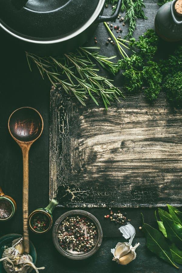 Matbakgrund med att laga mat pannan, nya smaktillsats för träsked och kryddor på mörk lantlig bakgrund, bästa sikt arkivfoton