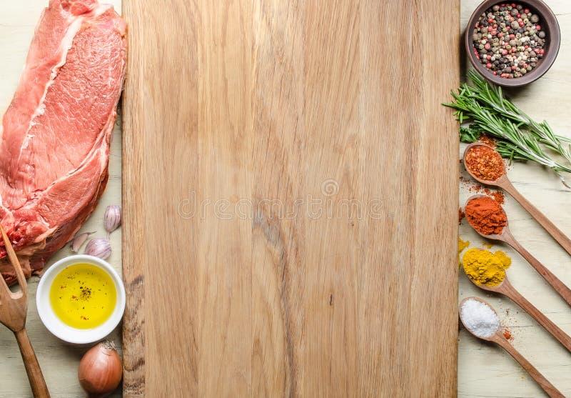 Matbakgrund med biffar och smaktillsats för rått kött royaltyfri bild