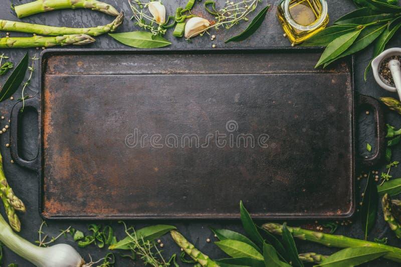 Matbakgrund med fritt utrymme för text Örter olivolja, kryddor runt om gjutjärn som steker brädet Top beskådar arkivfoton