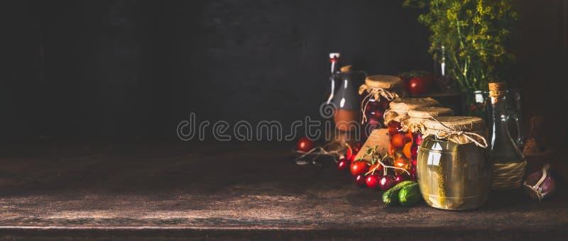 Matbakgrund med variation av bevarade jäste grönsaker och frukter från trädgård i exponeringsglaskrus på mörk lantlig bakgrund arkivbild