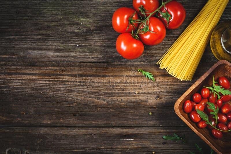 Matbakgrund: torr pasta, tomater, olivolja och kryddor royaltyfria foton