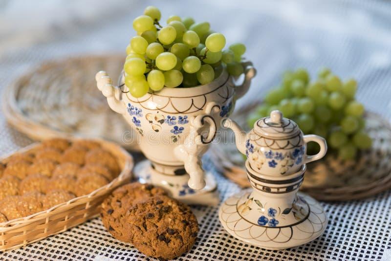 Matbilddruvor, kakor, tekanna och bordduk 2019 royaltyfri fotografi