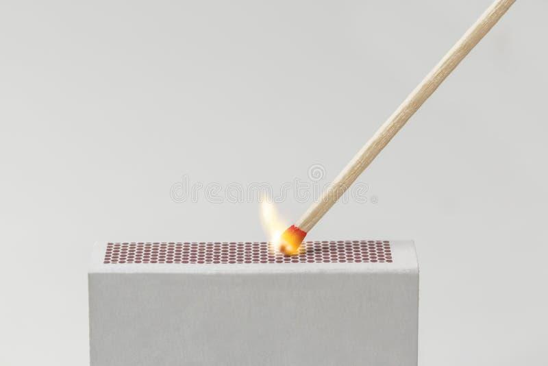 Match beleuchtet auf einer Streichholzschachtel lizenzfreies stockfoto