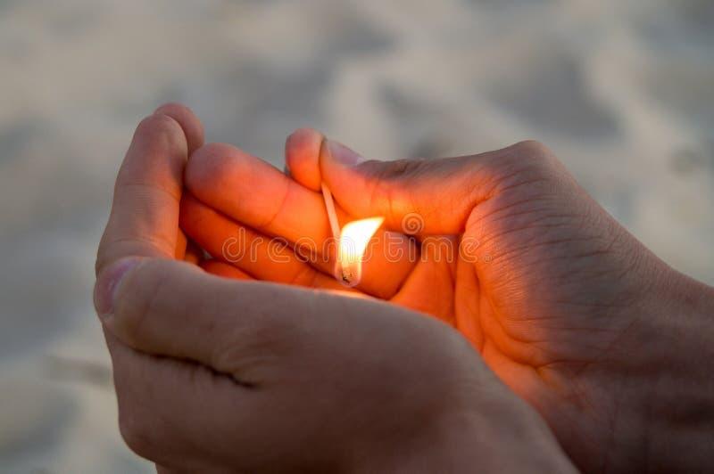 Match brûlant dans des mains La flamme du match indiquant l'haut photos stock