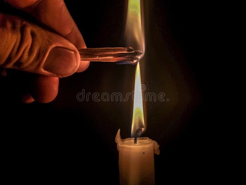 Match, das brennt, um eine Kerze zu beleuchten lizenzfreie stockfotos