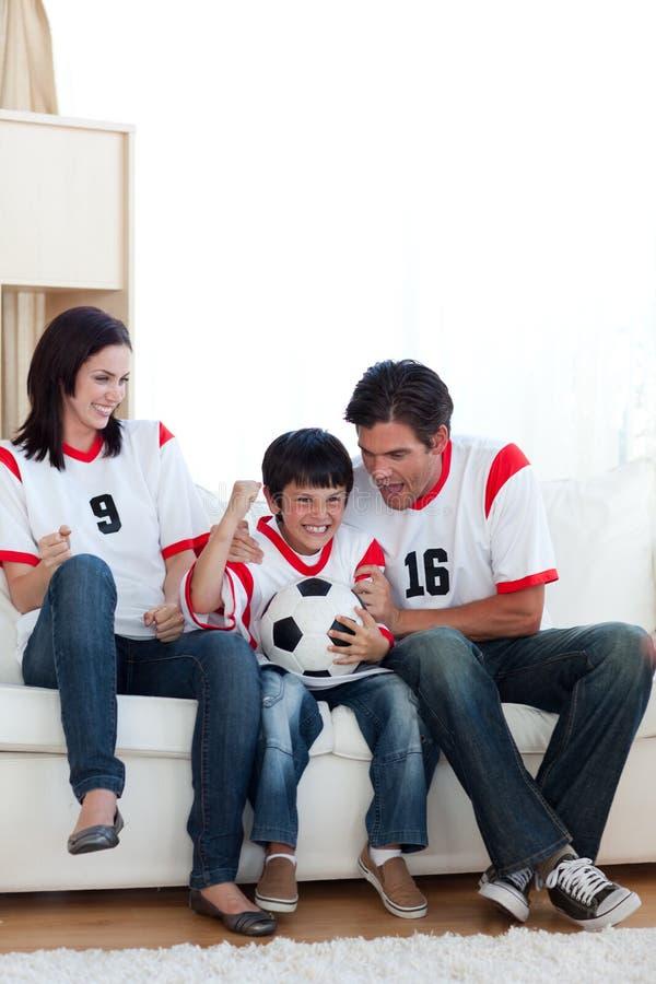 Match de football de observation de famille joyeuse sur le televisio image stock