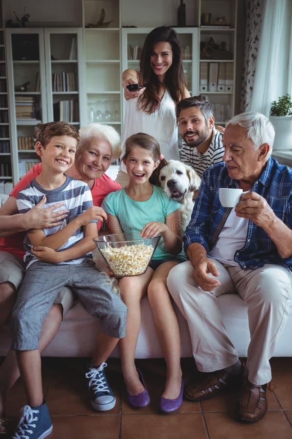 Match de football de observation de famille sur plusieurs générations heureuse à la télévision dans le salon photo stock