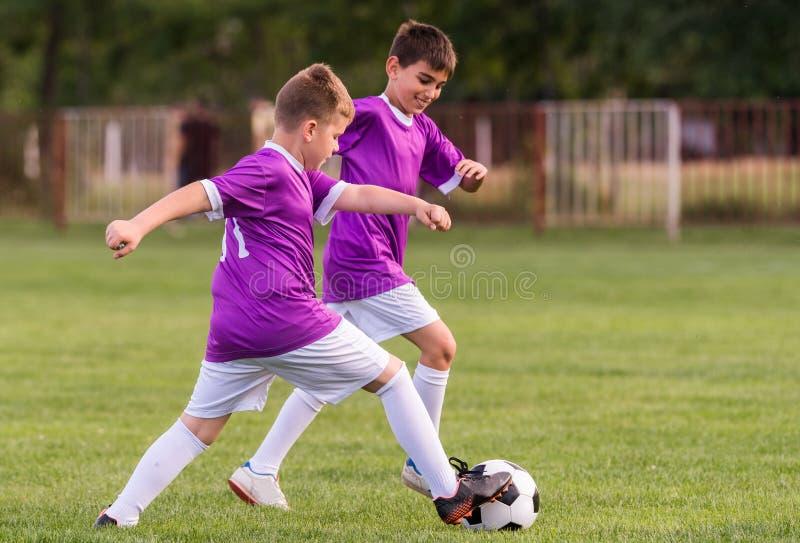 Match de football de joueurs d'enfants en bas âge sur le terrain de football image libre de droits