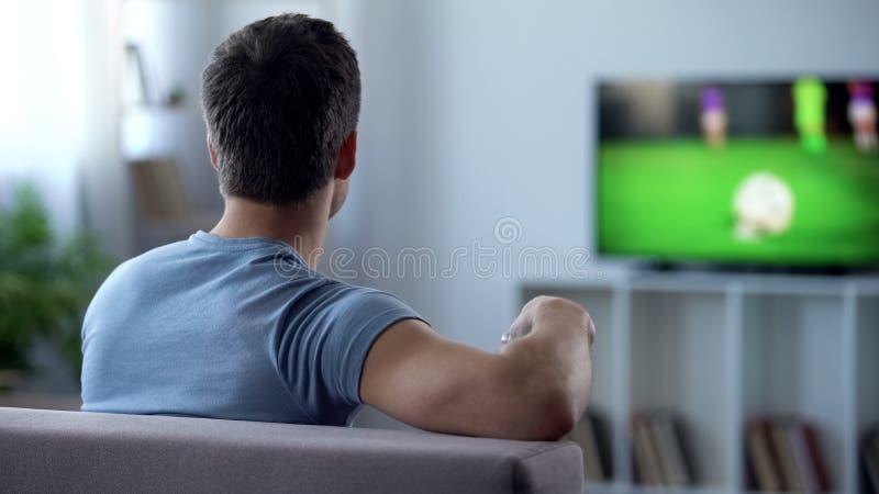 Match de football de observation de fan masculine à la TV, renversement par la télévision numérique de qualité inférieure image libre de droits