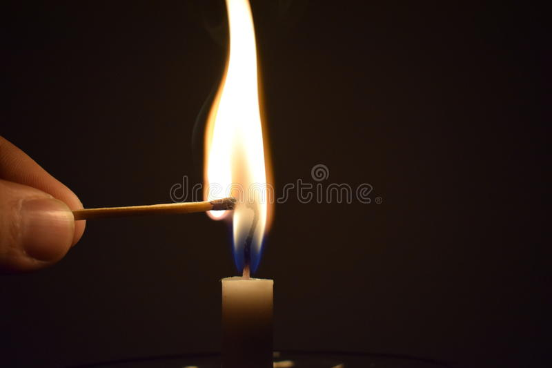 Match Stick Catching Fire from Burning Candle stock image