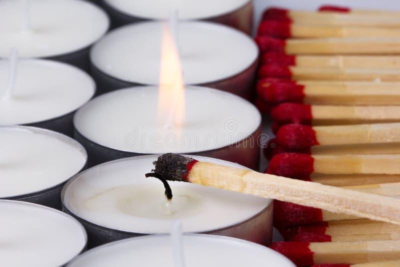 Match zündete weiße Kerzen an stockbilder