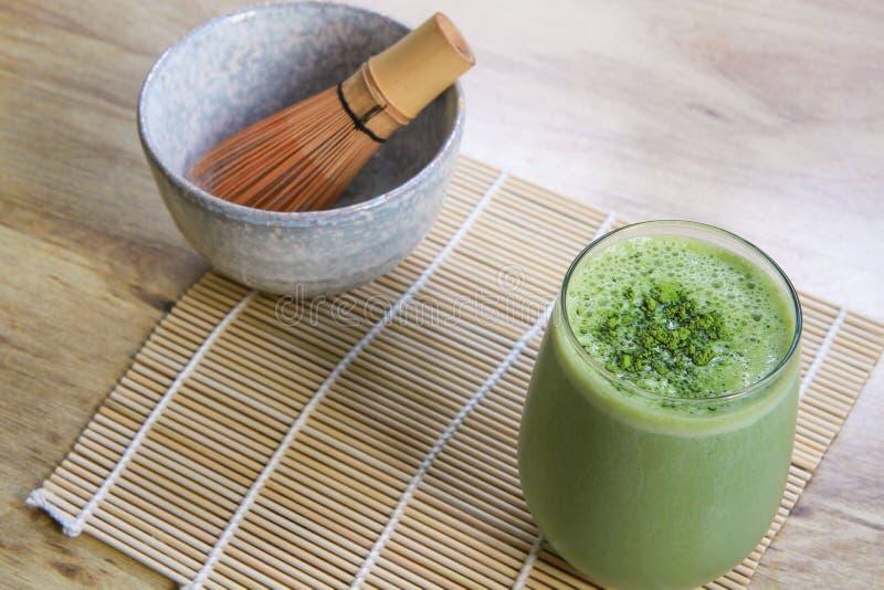 Matcha与石碗的绿茶圆滑的人和木在桌上的竹席子扫 免版税库存照片