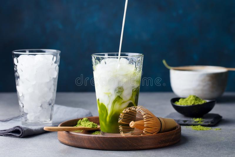 Matcha, πράσινη έκχυση τσαγιού πάγου τσαγιού στο ψηλό γυαλί στο ξύλινο πιάτο Γκρίζο υπόβαθρο πετρών στοκ φωτογραφίες με δικαίωμα ελεύθερης χρήσης