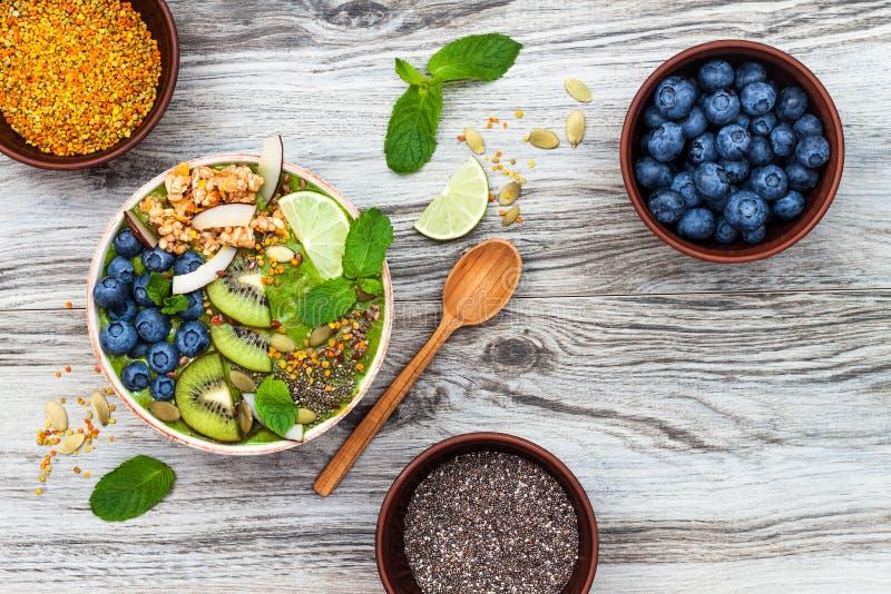 Matcha绿茶早餐superfoods圆滑的人滚保龄球冠上与chia、胡麻和南瓜籽,蜂花粉,格兰诺拉麦片,椰子剥落 免版税库存图片