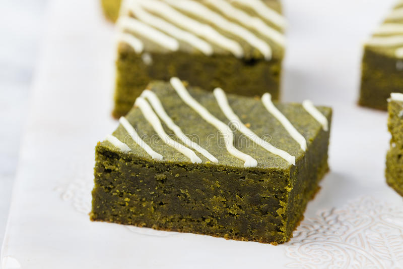 Matcha绿茶果仁巧克力蛋糕用在一块白色板材的白色巧克力 背景灰色石头 免版税库存照片