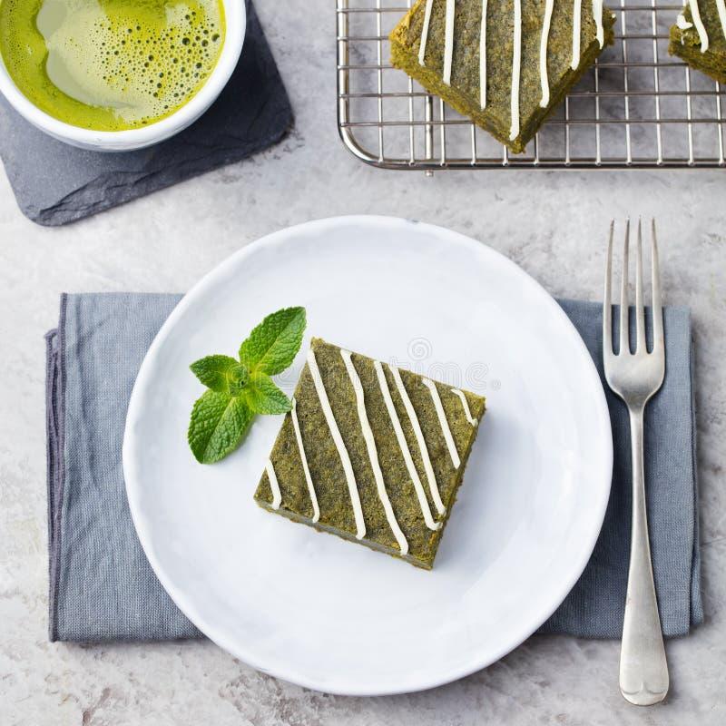 Matcha绿茶果仁巧克力蛋糕用在白色板材灰色石背景的白色巧克力 免版税库存照片
