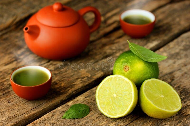 Matcha grönt te, nya limefrukter, teblad på en gammal lantlig woode arkivfoto