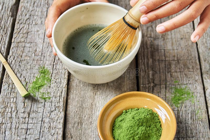 Matcha green tea accessoires on the rough wooden boards with girl`s hands preparing matcha tea in a clay bowl. Matcha green tea accessoires on the rough wooden royalty free stock images