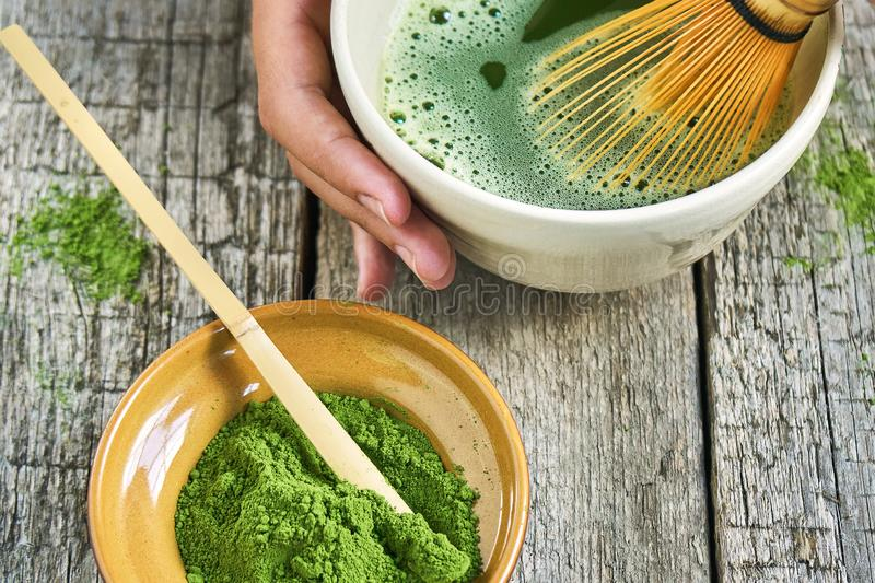 Matcha green tea accessoires on the rough wooden boards with girl`s hands preparing matcha tea in a clay bowl. Matcha green tea accessoires on the rough wooden royalty free stock photos