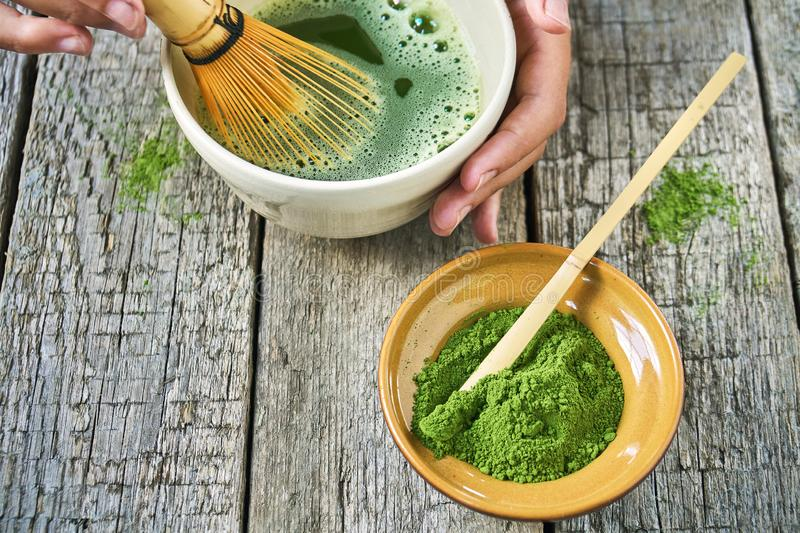 Matcha green tea accessoires on the rough wooden boards with girl`s hands preparing matcha tea in a clay bowl. Matcha green tea accessoires on the rough wooden royalty free stock photography