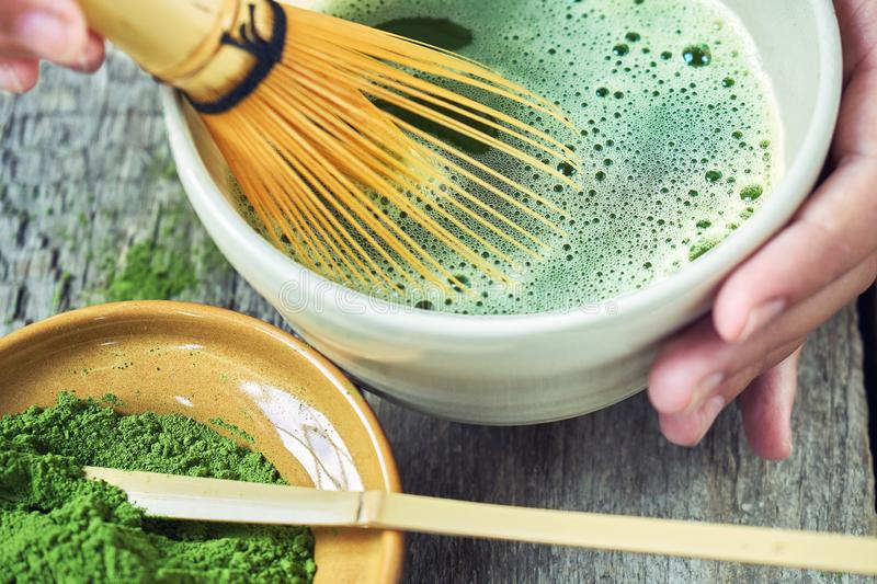 Matcha green tea accessoires on the rough wooden boards with girl`s hands preparing matcha tea in a clay bowl. Matcha green tea accessoires on the rough wooden royalty free stock photo
