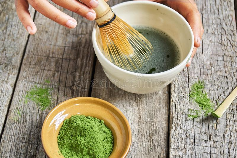 Matcha green tea accessoires on the rough wooden boards with girl`s hands preparing matcha tea in a clay bowl. Matcha green tea accessoires on the rough wooden stock photos