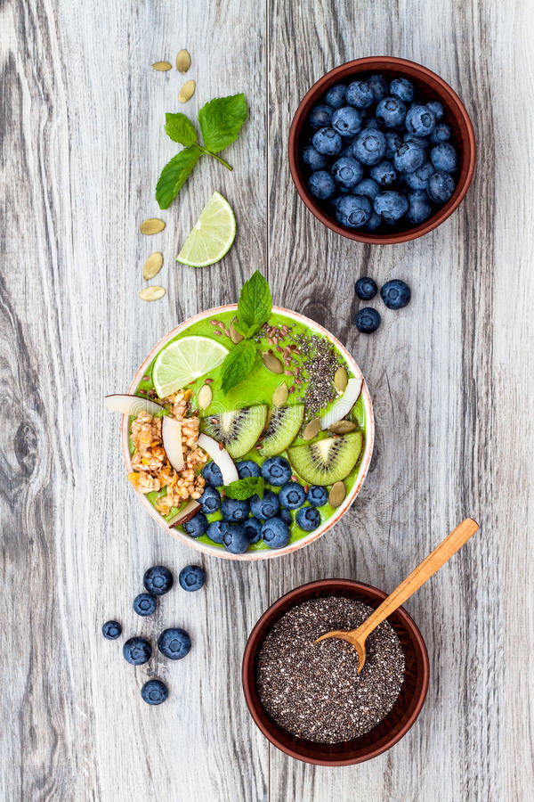 Matcha green tea breakfast superfoods smoothies bowl topped with chia, flax and pumpkin seeds, bee pollen, granola, coconut flakes. Kiwi and blueberries royalty free stock images