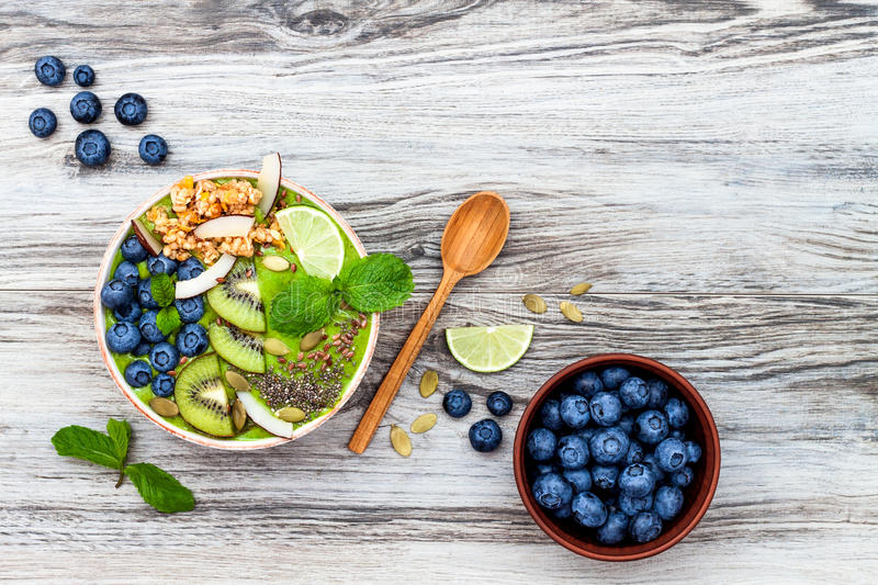 Matcha green tea breakfast superfoods smoothies bowl topped with chia, flax and pumpkin seeds, bee pollen, granola, coconut flakes. Kiwi and blueberries royalty free stock photos