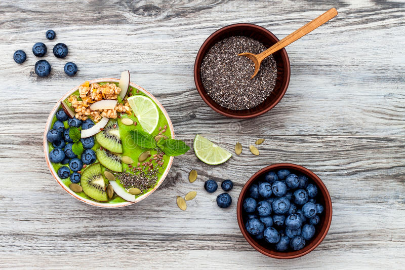 Matcha green tea breakfast superfoods smoothies bowl topped with chia, flax and pumpkin seeds, bee pollen, granola, coconut flakes. Kiwi and blueberries stock photo