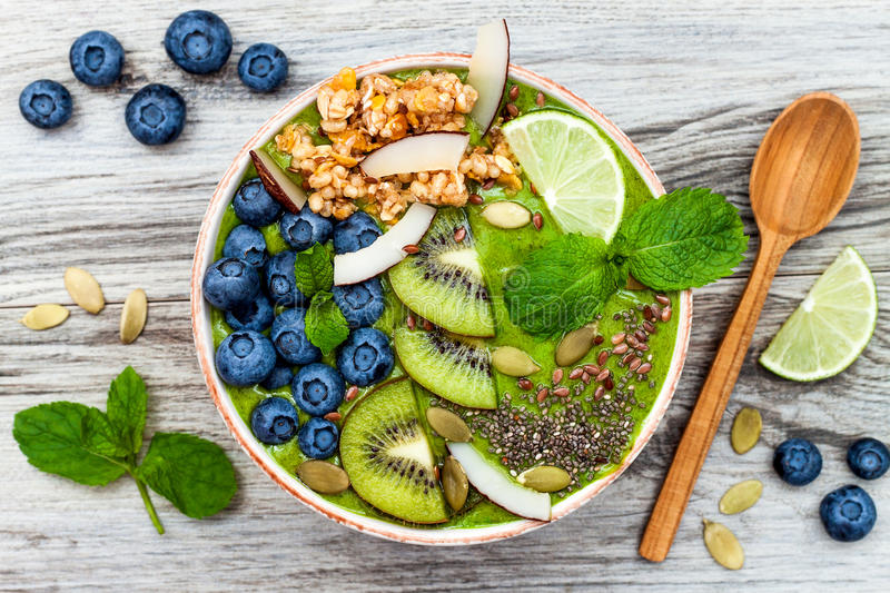 Matcha green tea breakfast superfoods smoothies bowl topped with chia, flax and pumpkin seeds, bee pollen, granola, coconut flakes. Kiwi and blueberries stock photos