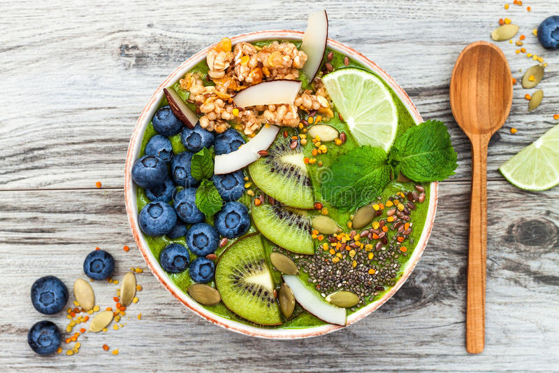 Matcha green tea breakfast superfoods smoothies bowl topped with chia, flax and pumpkin seeds, bee pollen, granola, coconut flakes. Kiwi and blueberries stock images