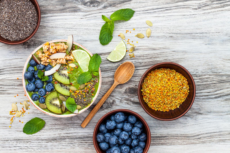 Matcha green tea breakfast superfoods smoothies bowl topped with chia, flax and pumpkin seeds, bee pollen, granola, coconut flakes. Kiwi and blueberries royalty free stock photography