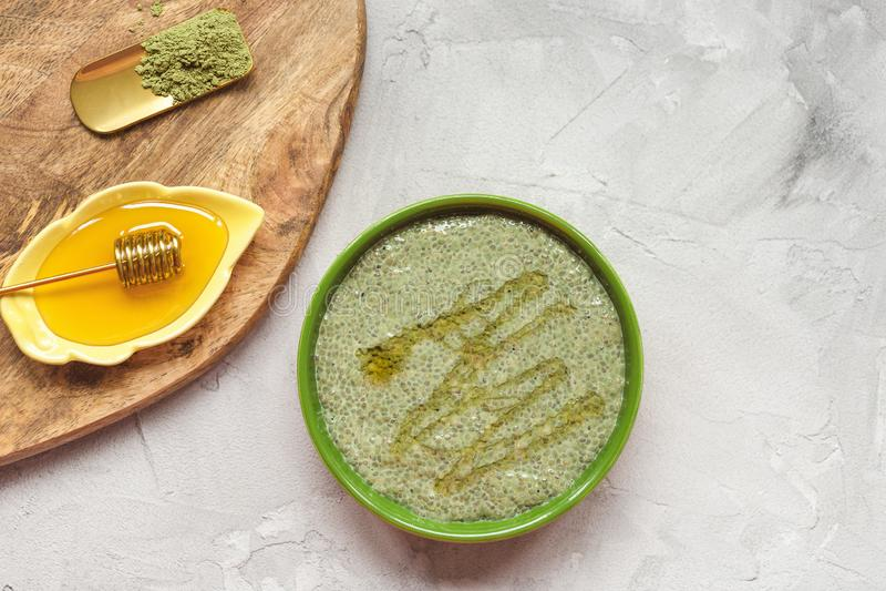 Matcha green tea chia seed pudding bowl with honey. Superfood and vegan concept. Matcha green tea chia seed pudding bowl and honey. Overhead, top view, flat lay stock photos