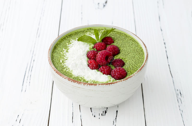 Matcha green tea chia seed pudding bowl, vegan dessert with raspberry and coconut milk. Overhead, top view, flat lay. Matcha green tea chia seed pudding bowl royalty free stock photography
